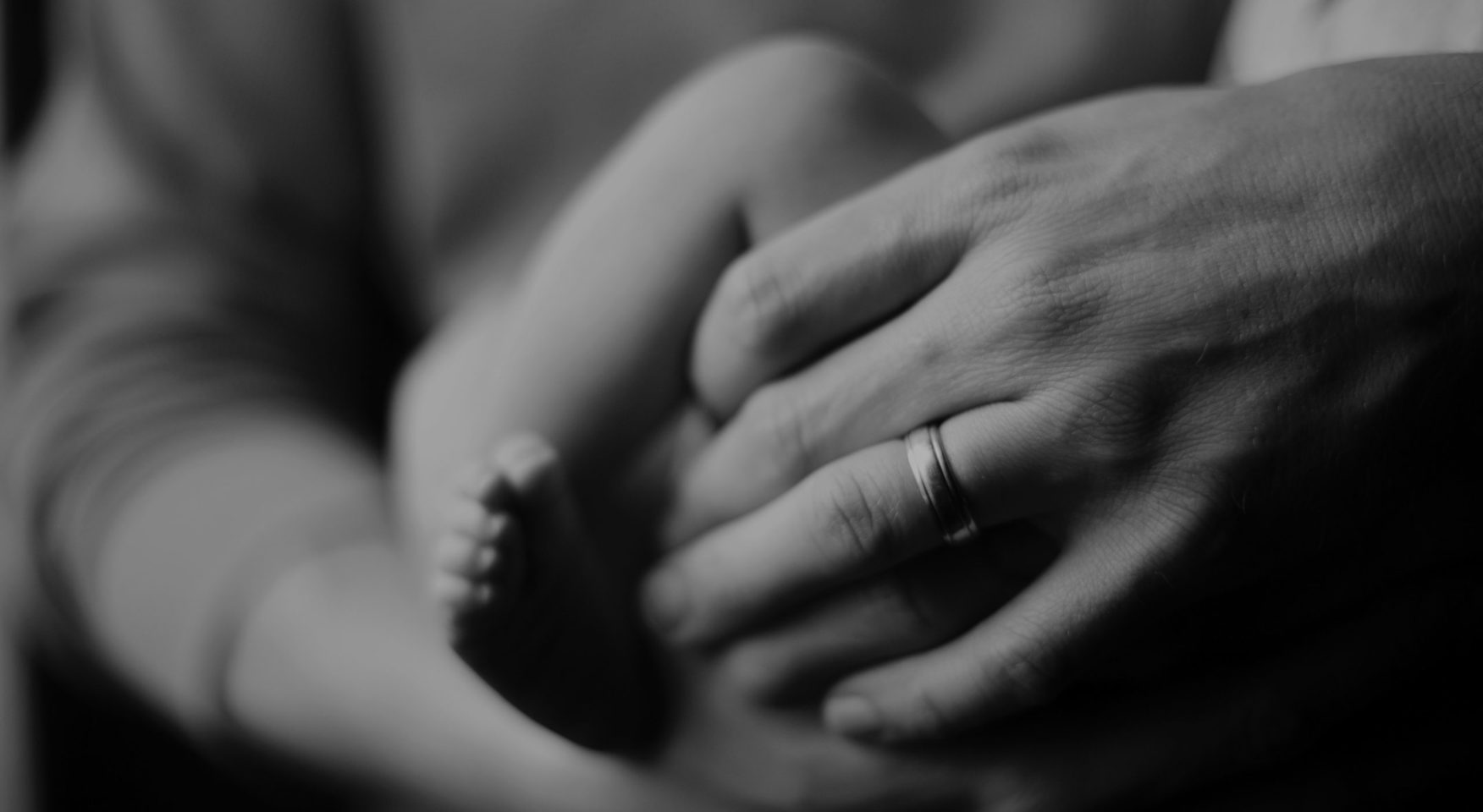 Adult holding baby closeup of hands and feet