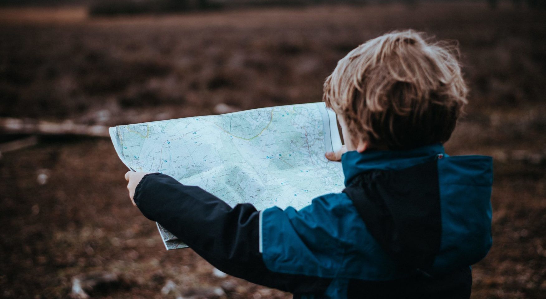 boy holding a map while standing in a field