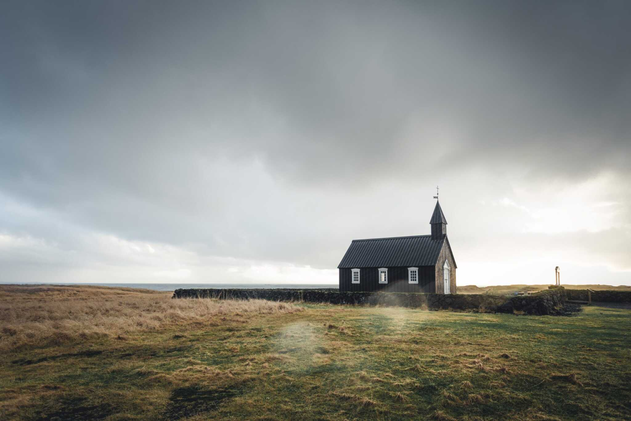 wooden church under stormy sky in a large meadow
