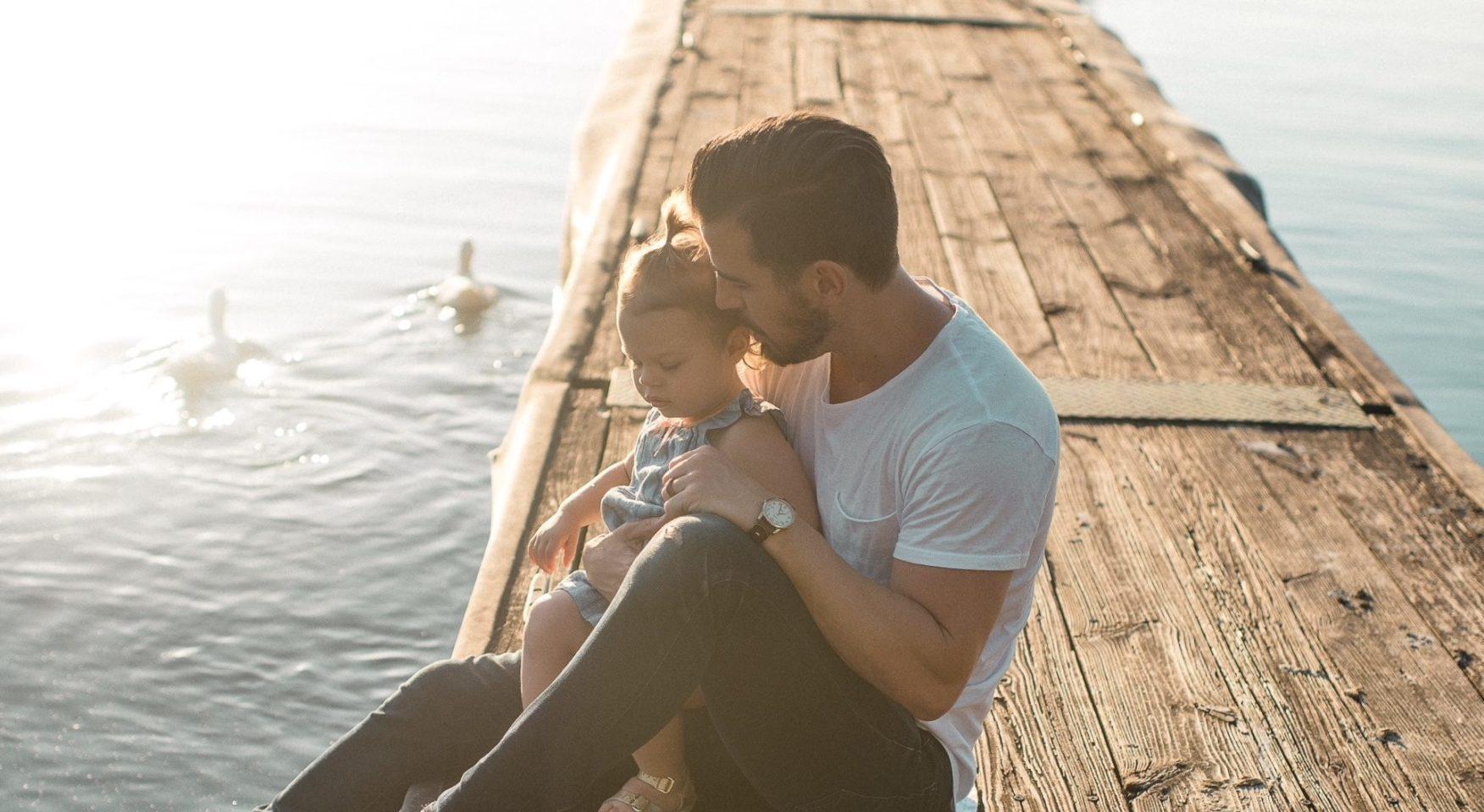 Dad holding toddler daughter sitting on lake pier