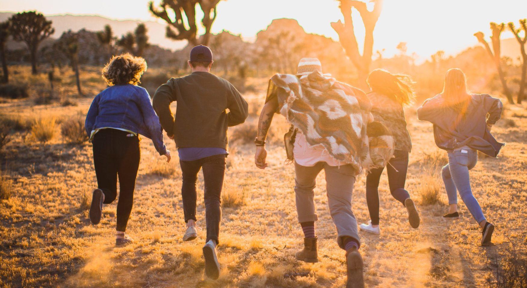 People running through the desert at sunset