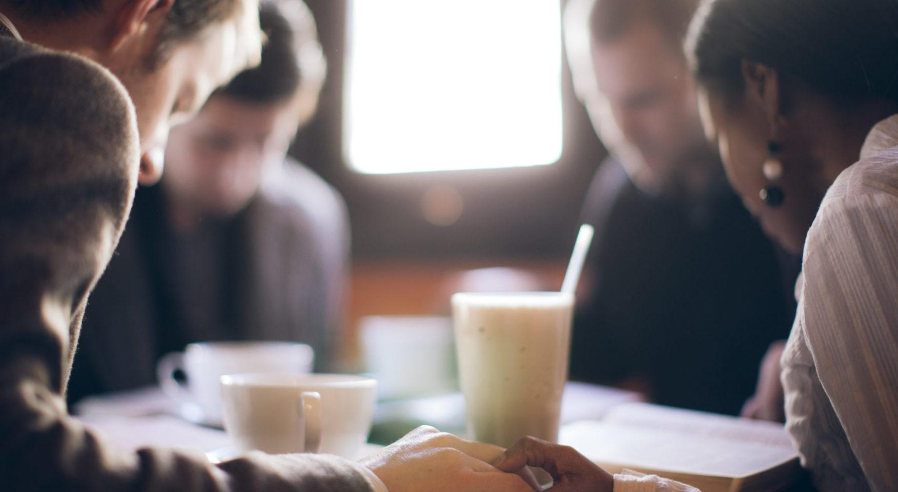 Group of people praying at table with milkshake