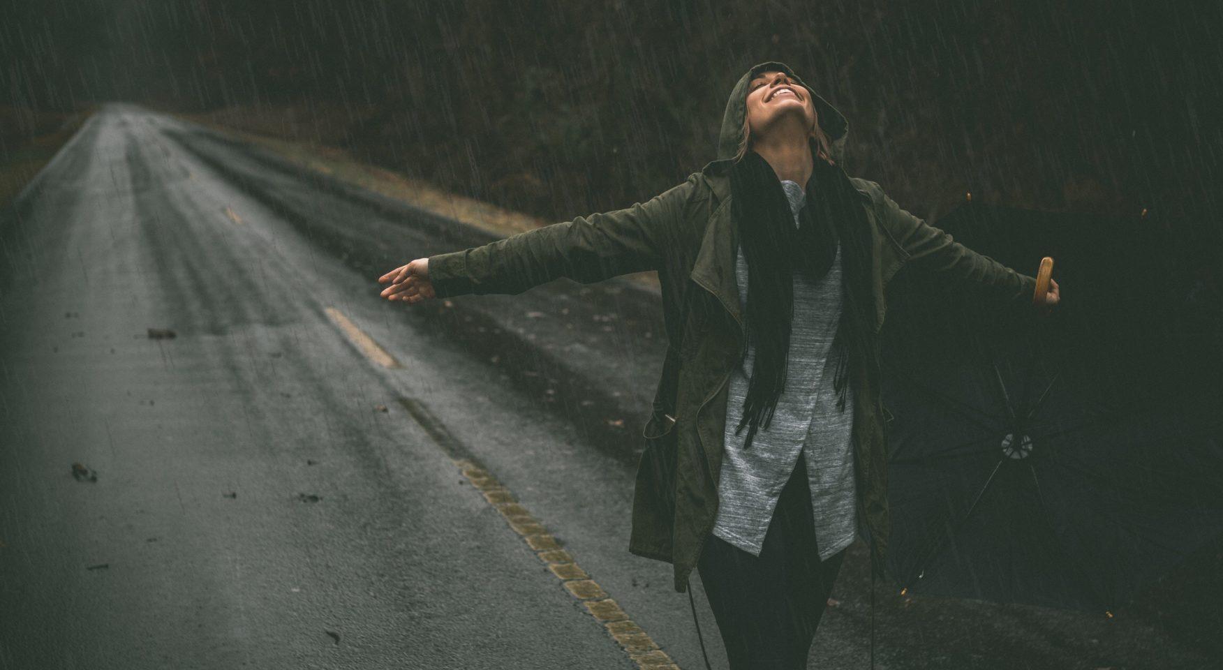 happy woman standing on rainy road
