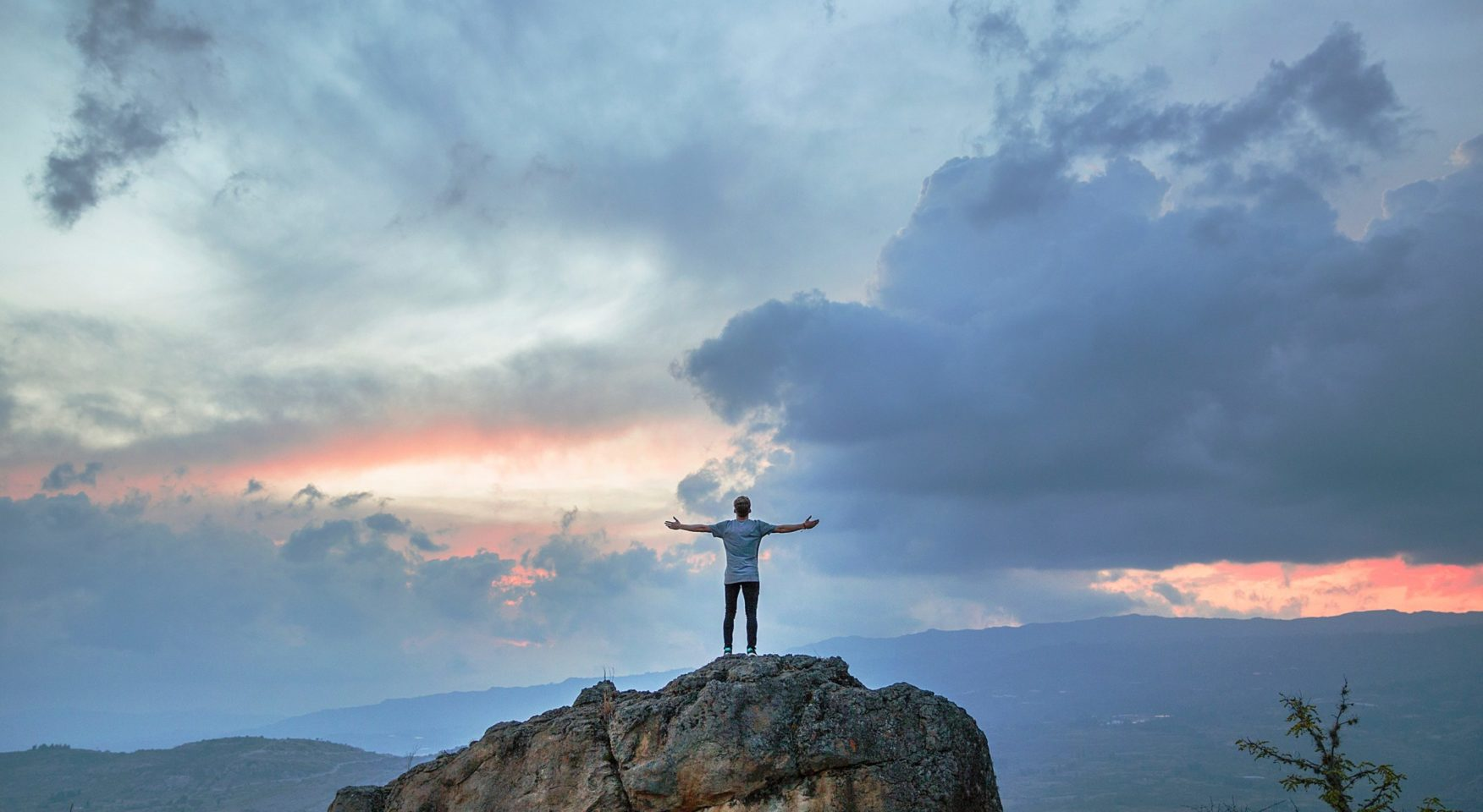 Man standing with his arms open atop rock