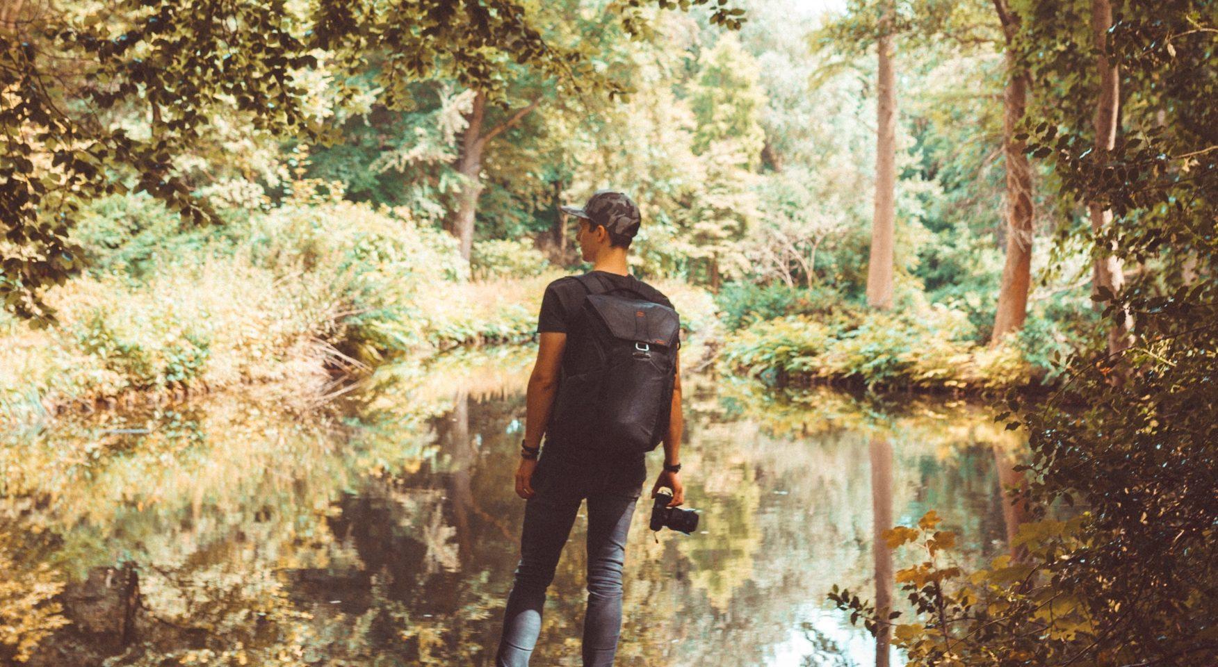 Man wearing backpack and holding camera walking through swamp