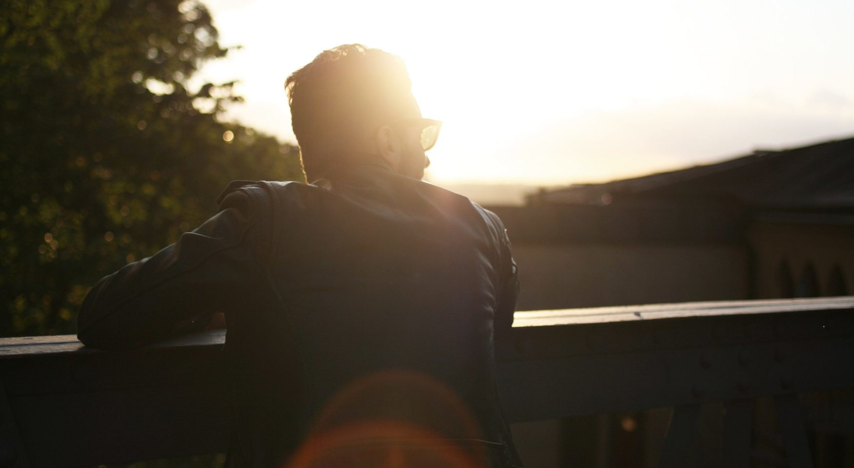 Man with sunglasses and black leather jacket staring at bright sun