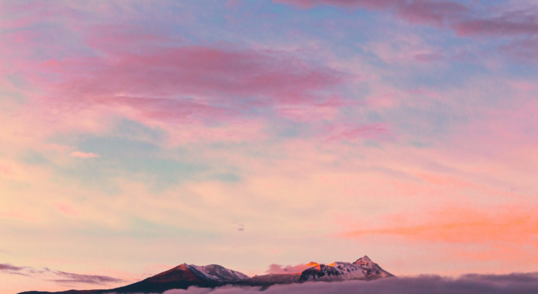 Pastel multi-colored sky above the tops of rocky mountains