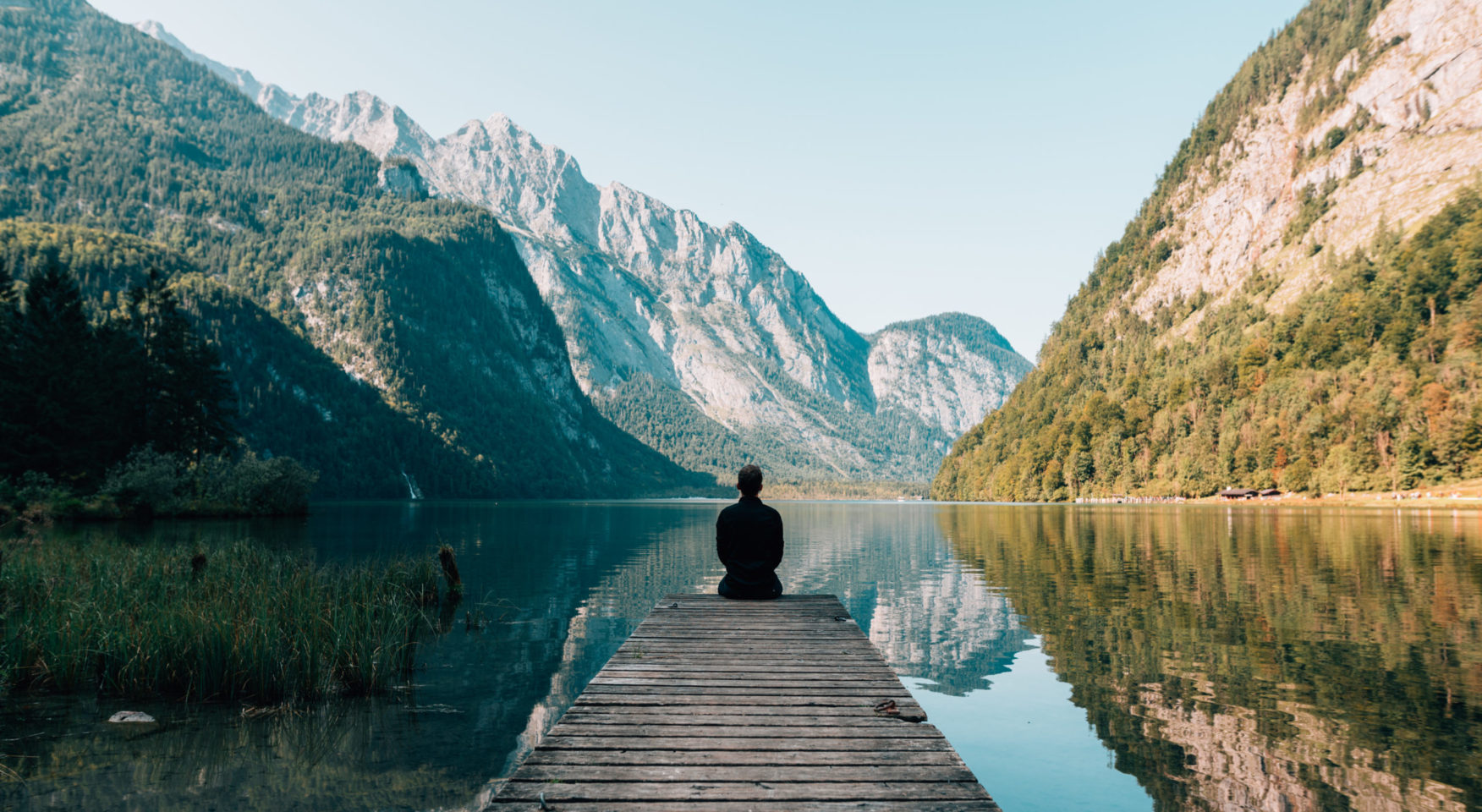 Person sitting on a dock at mountain lake