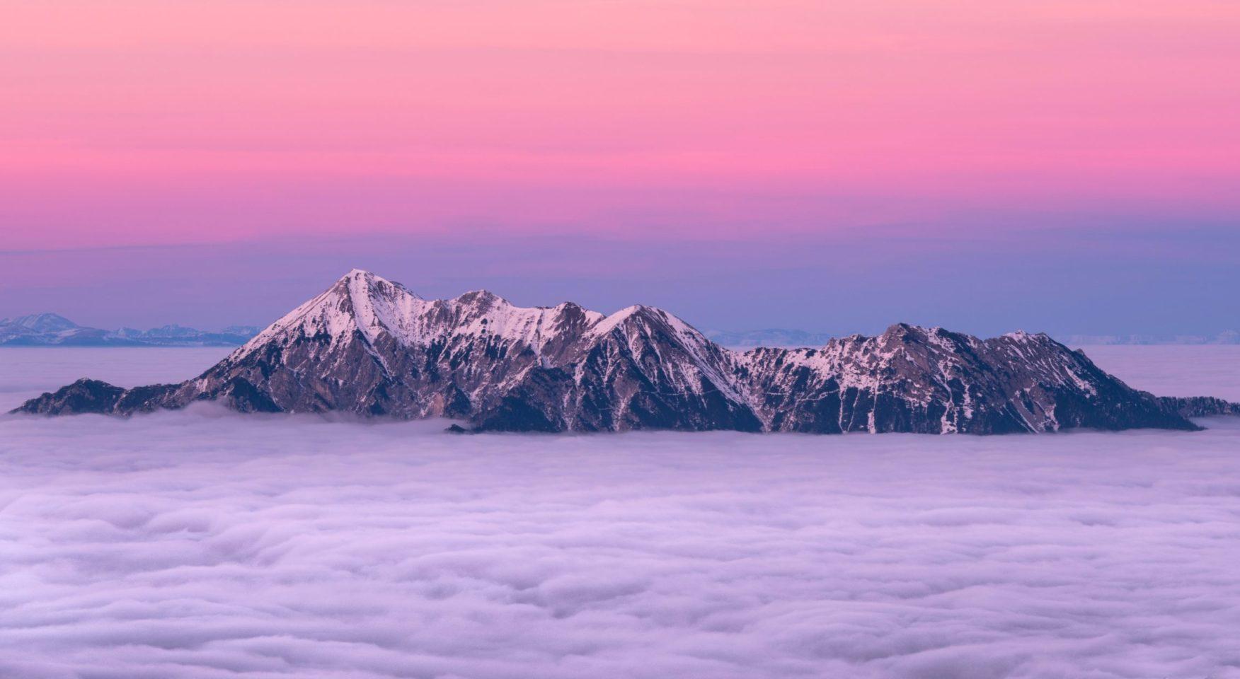 Rocky mountain tops peeking through clouds against briight purple pink sky