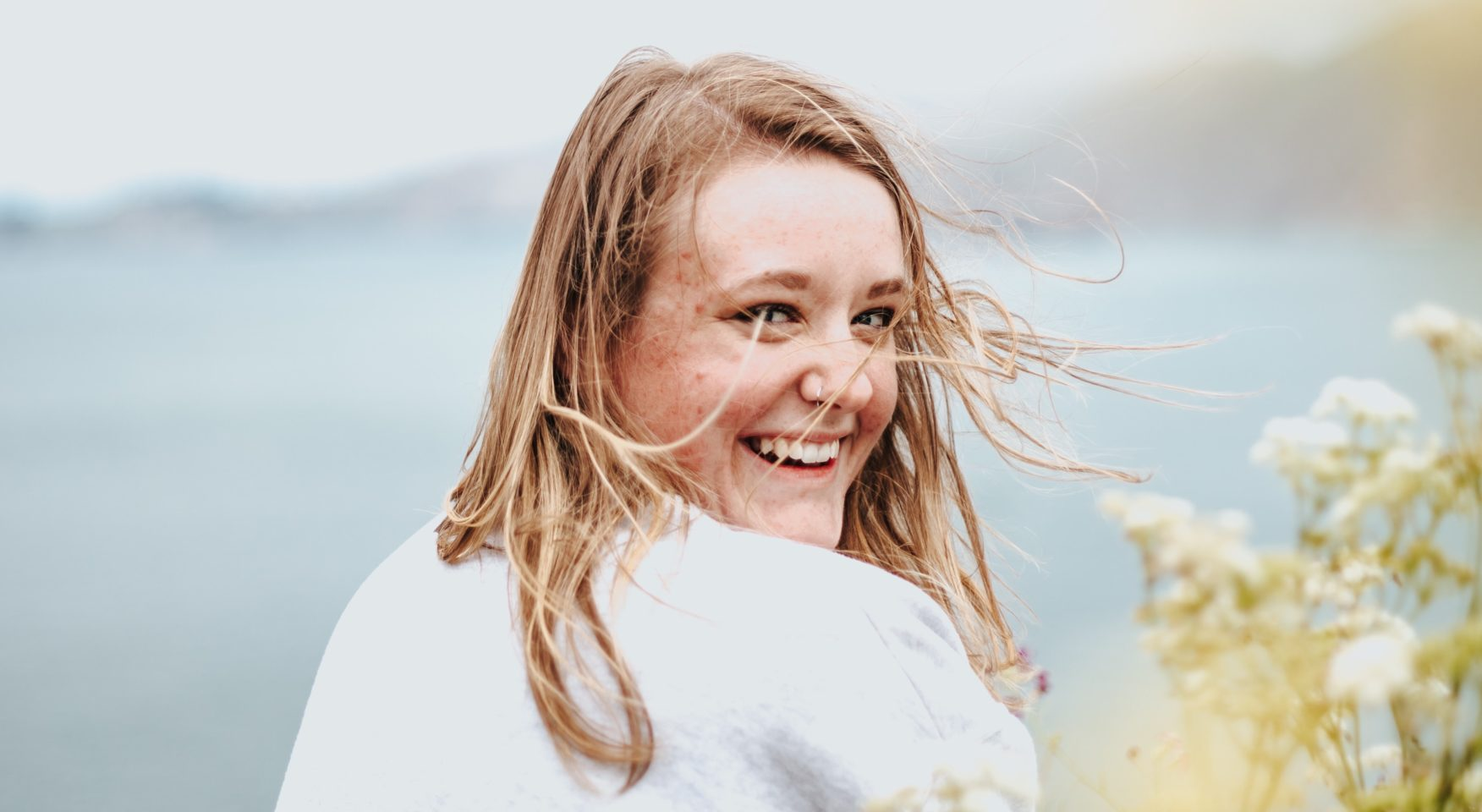 smiling woman with strawberry blonde hair on a windy day