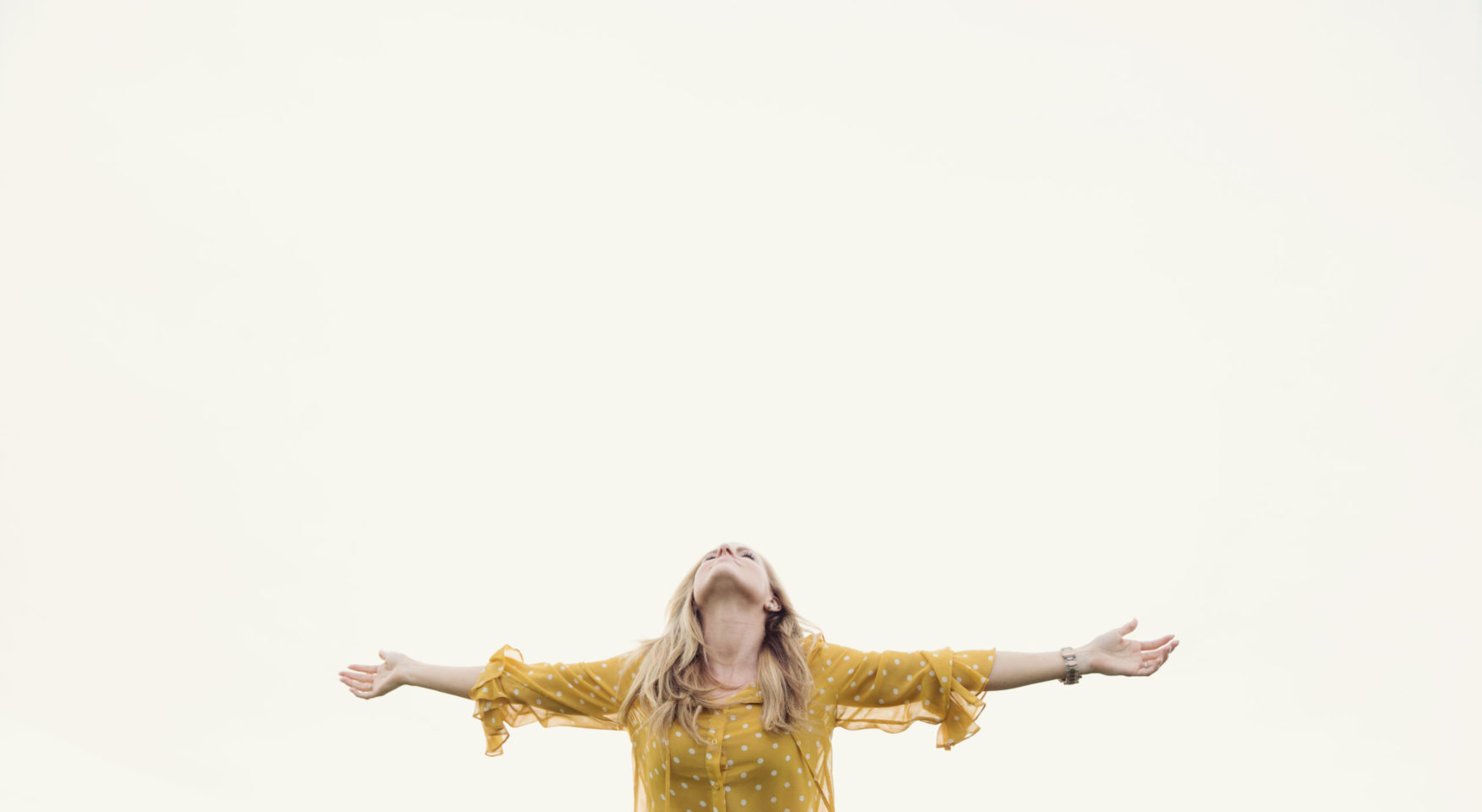 Woman in yellow shirt with open arms