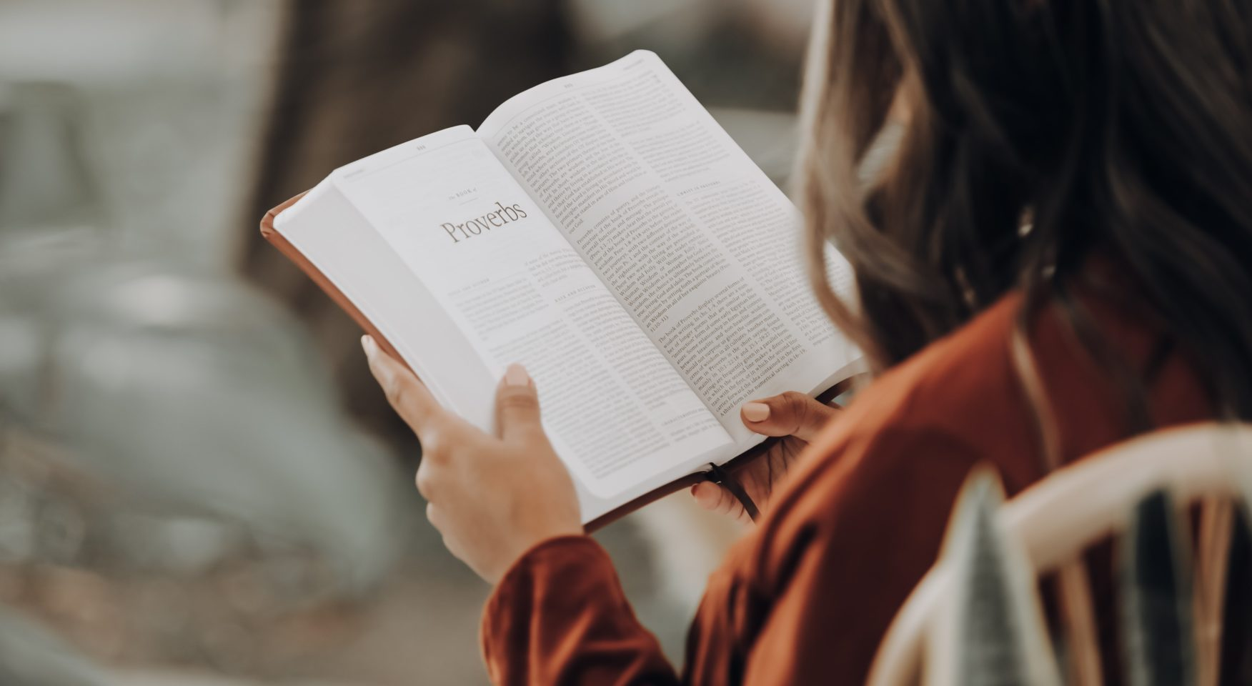 Woman in orange shirt reading Bible