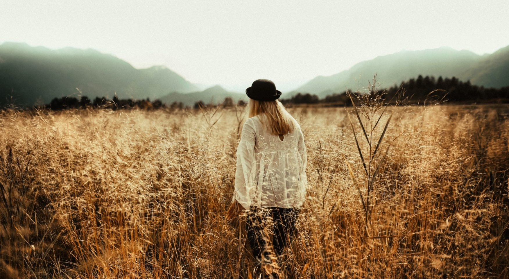Woman wearing white lacy blouse and black hat walking through meadow of brown brush