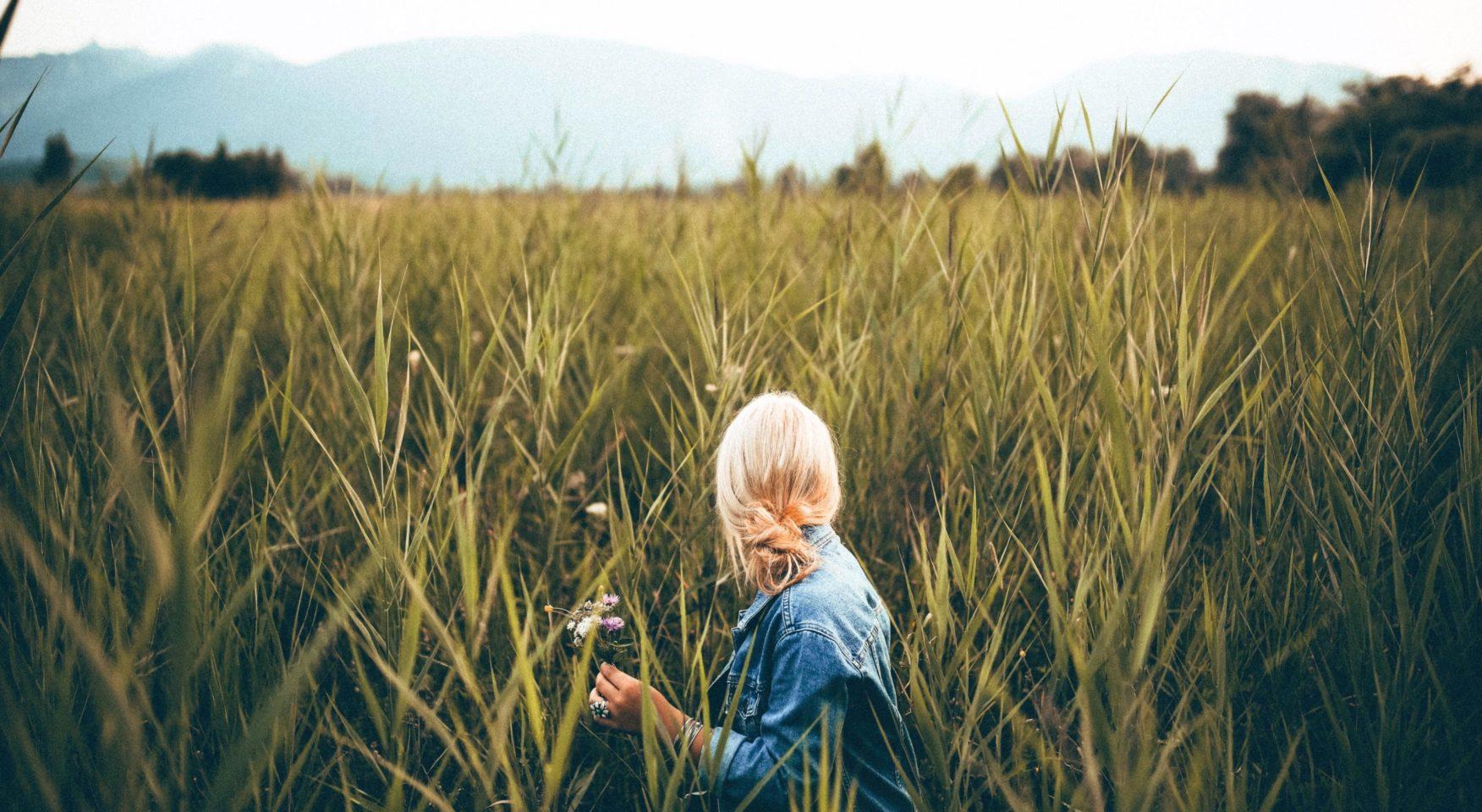 blonde woman in field of reeds
