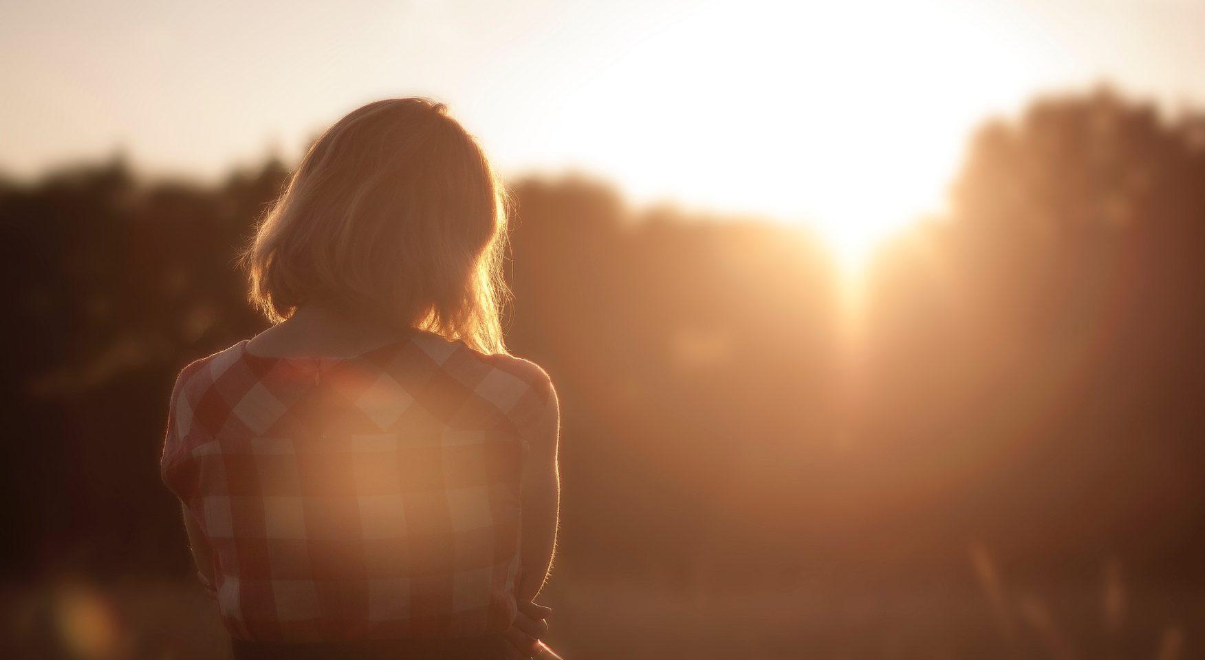 woman standing in field in golden sunlight