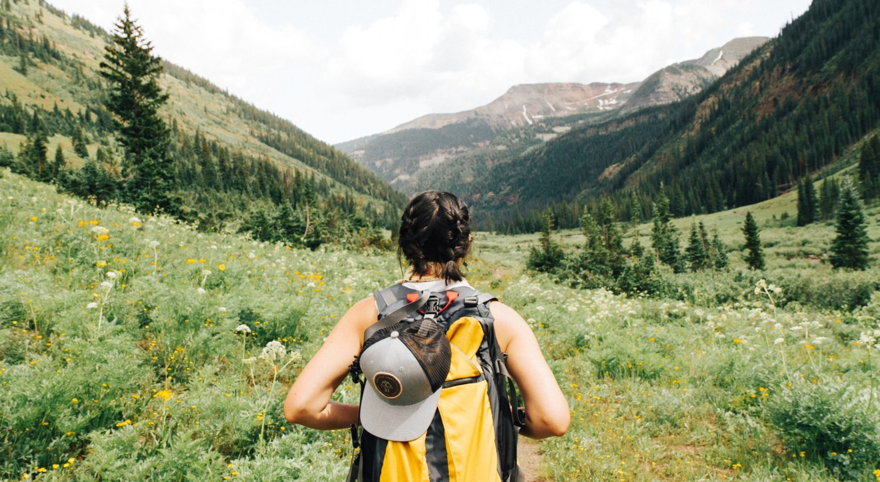 woman hiking with yellow backpack