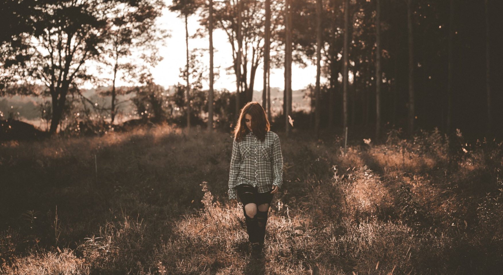 Sepia-tinted photo of woman in plaid shirt walking in forest