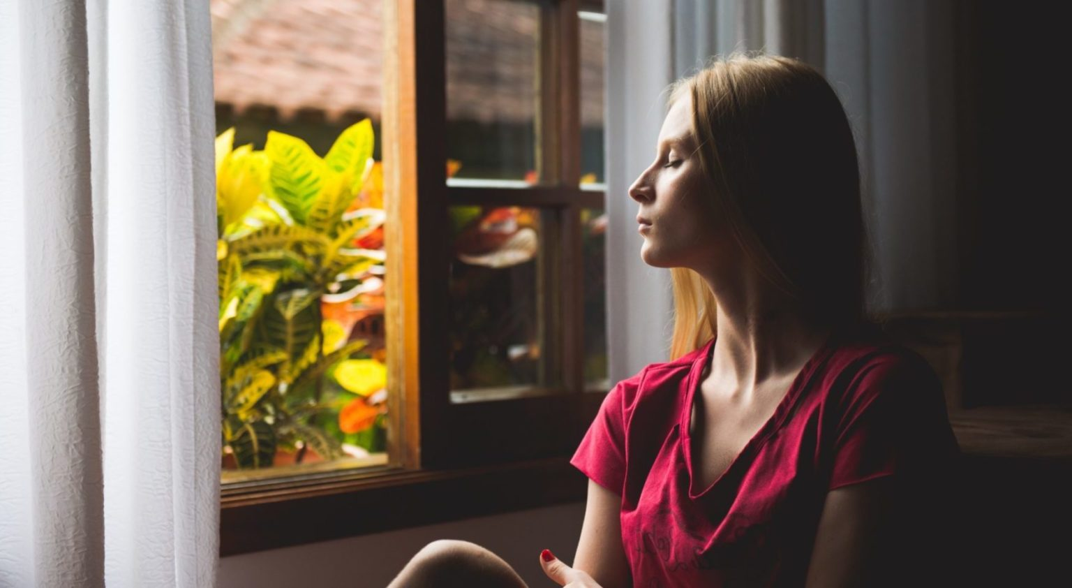 Woman in red blouse staring out of window