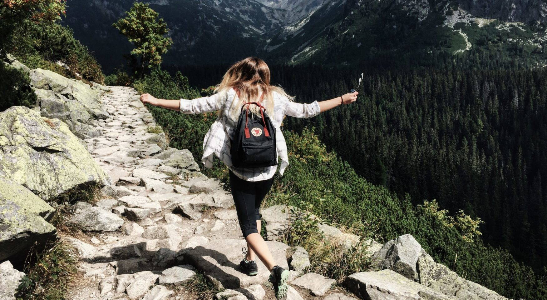 woman hiking on mountain rocks