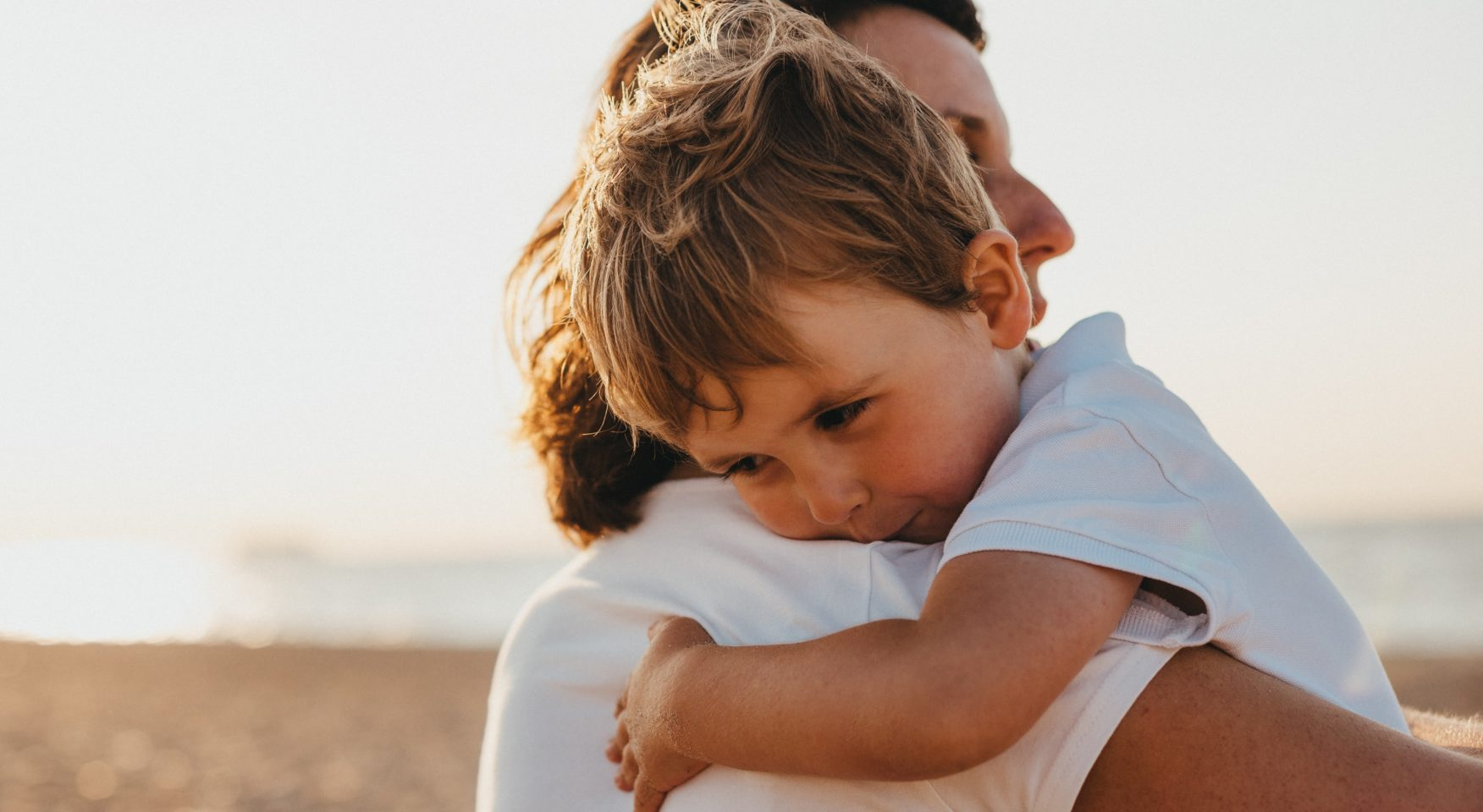 young son hugging parent on beach
