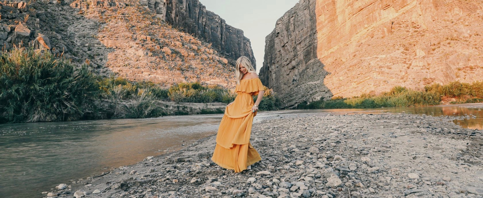 Ellie Holcomb standing on a riverbank in a canyon