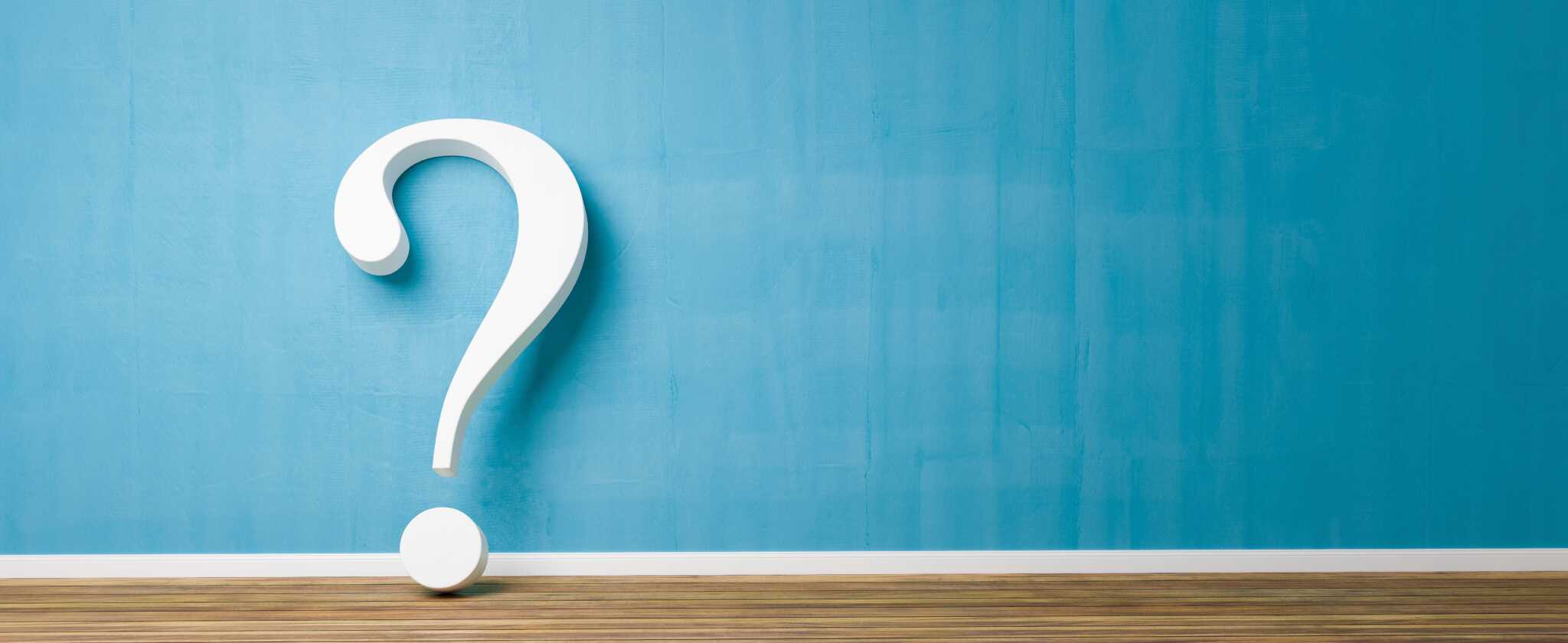 white question mark against blue wall